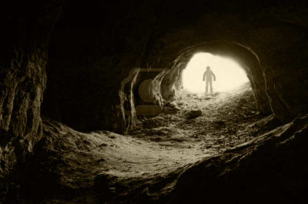 11386256-man-standing-in-front-of-a-cave-entrance